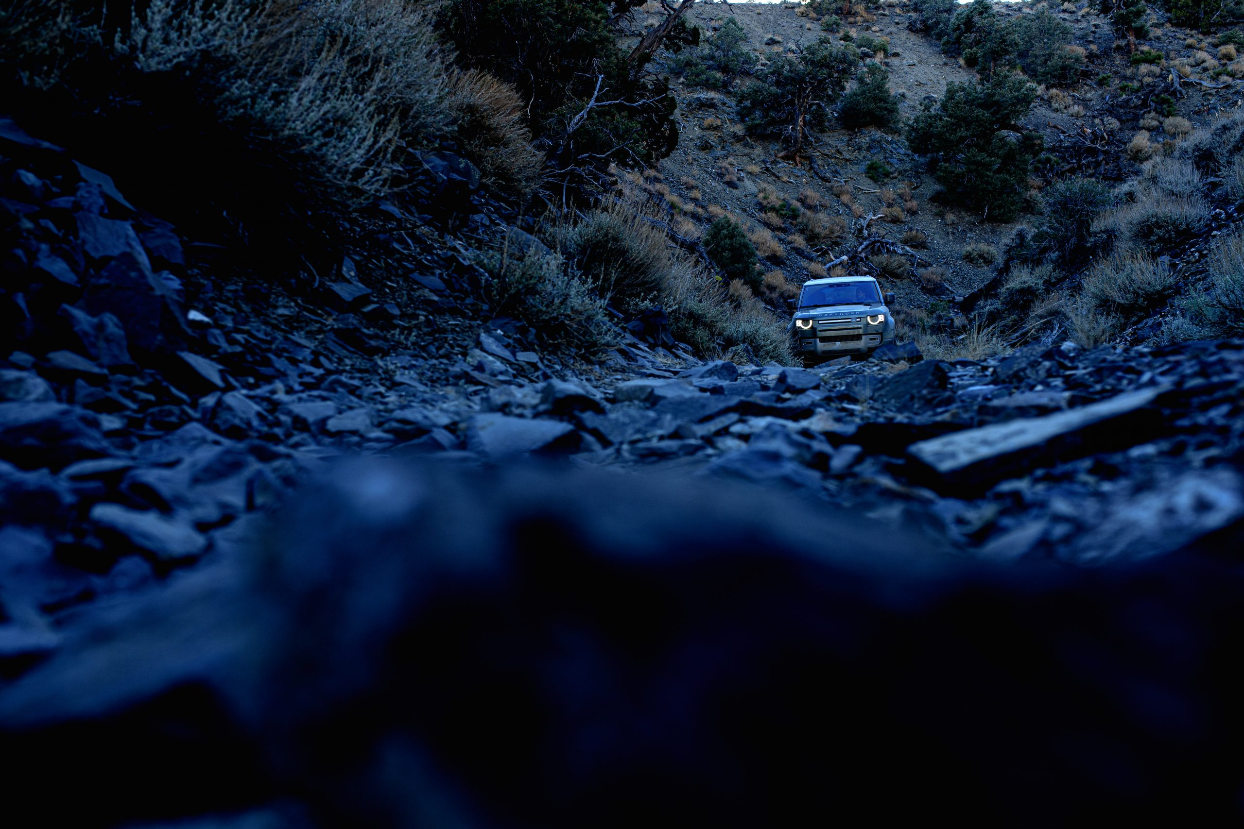 land rover defender front on rocky trail