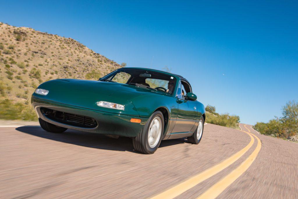 green mazda na miata driving action in desert