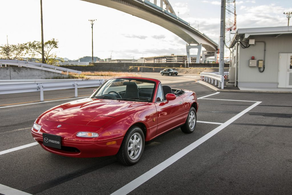 red na miata front three-quarter parked highway overpass
