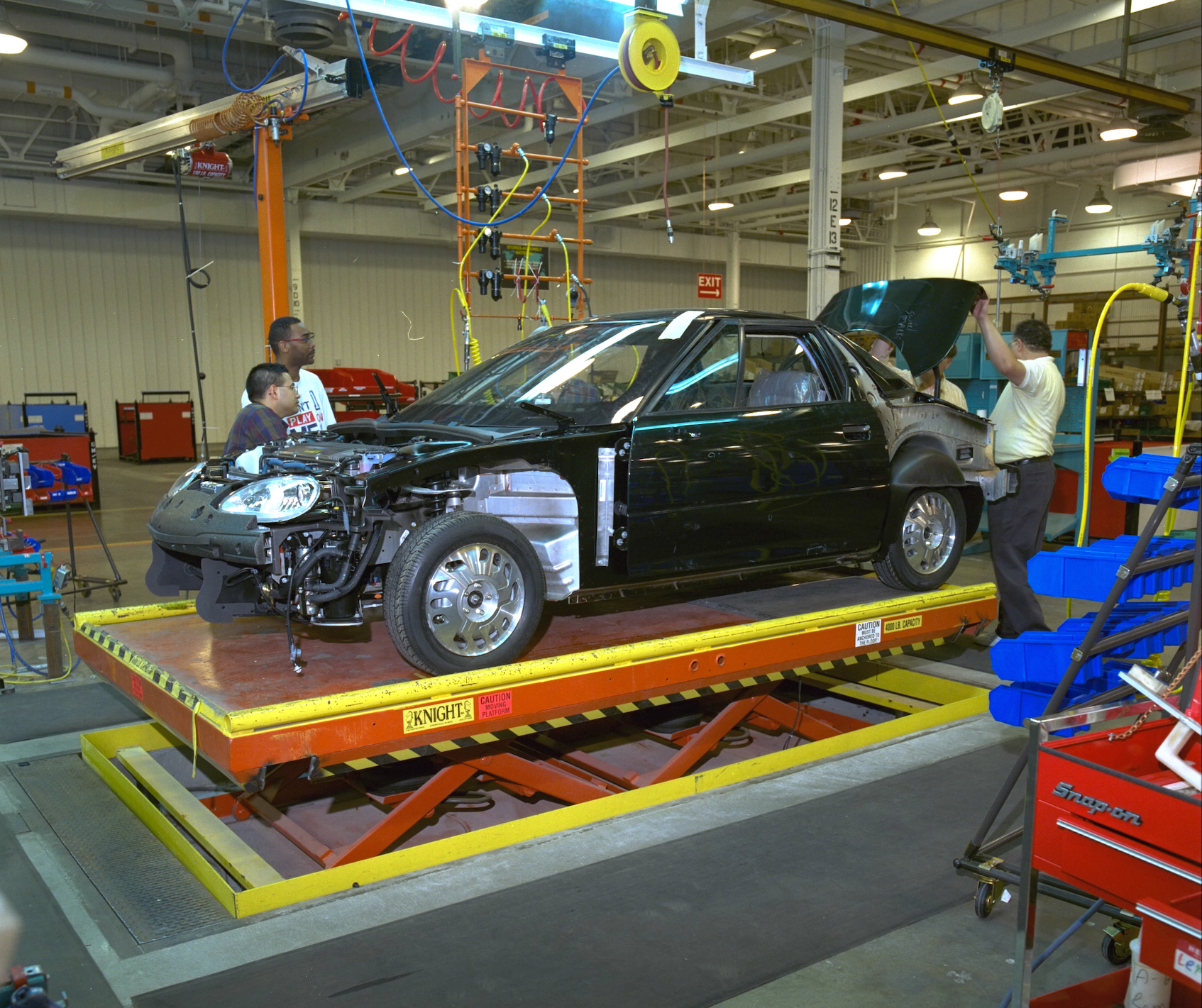Workers assembling early GM electric car
