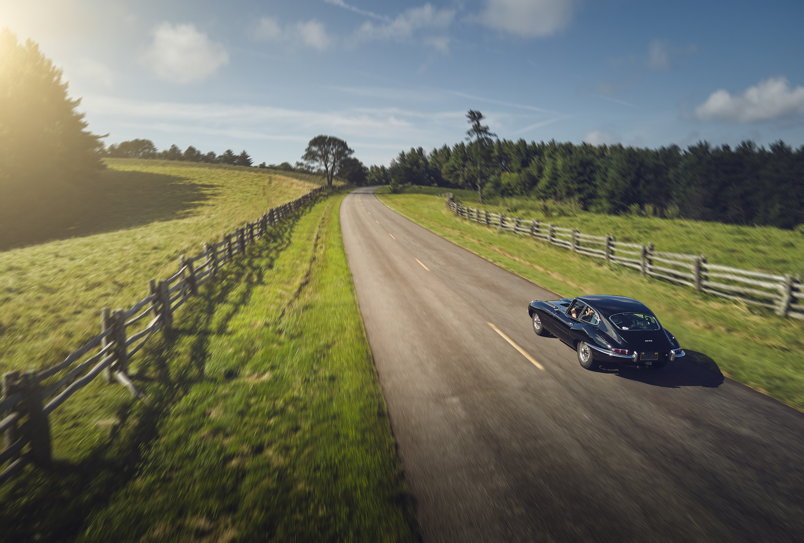 Jaguar E-Type rural road rear three-quarter action
