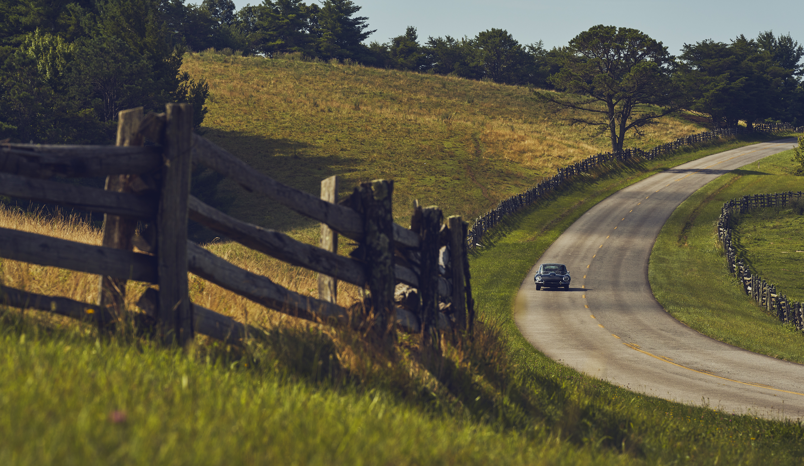 Jaguar E-Type front rural road fence