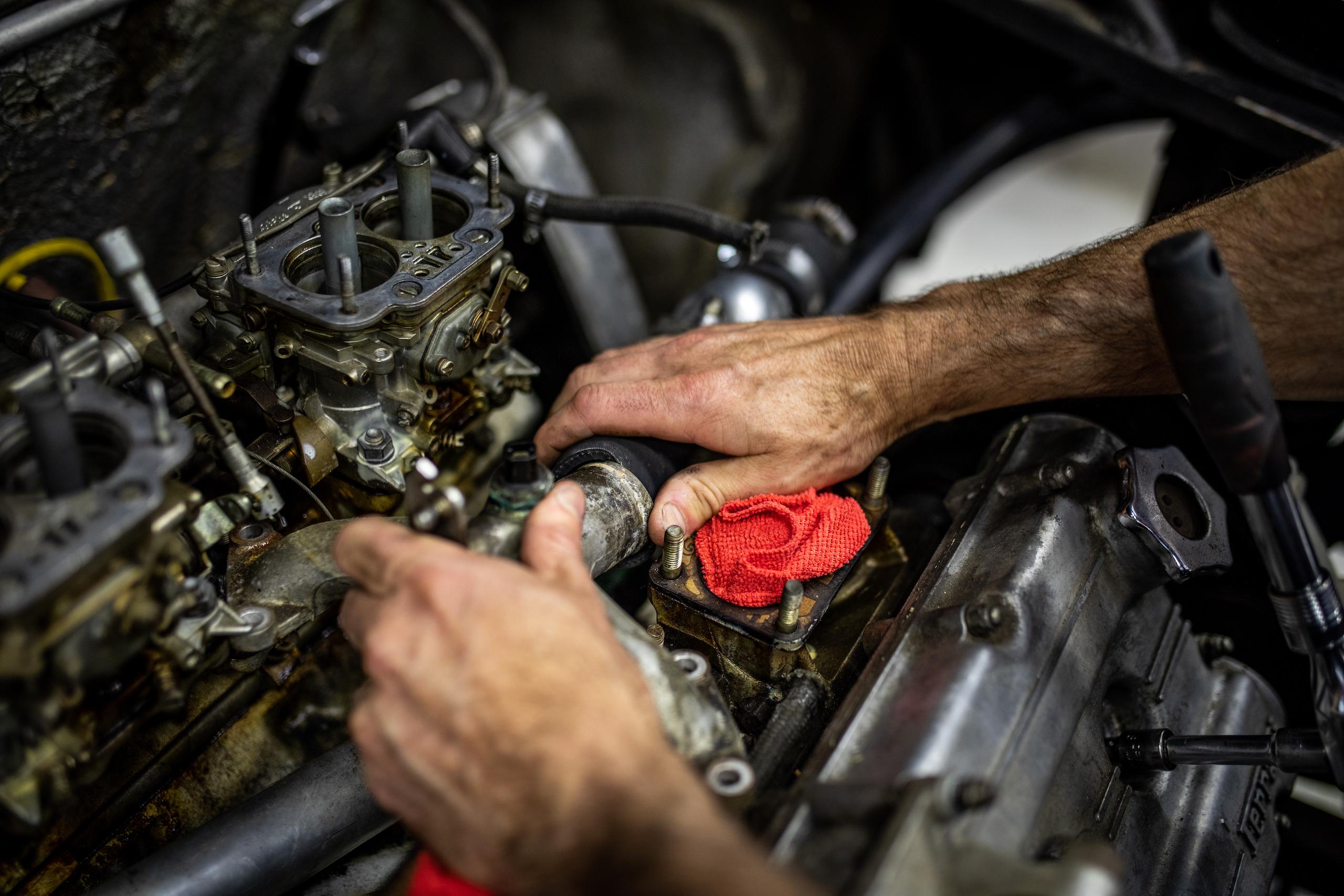 Ferrari Dino engine hands working close