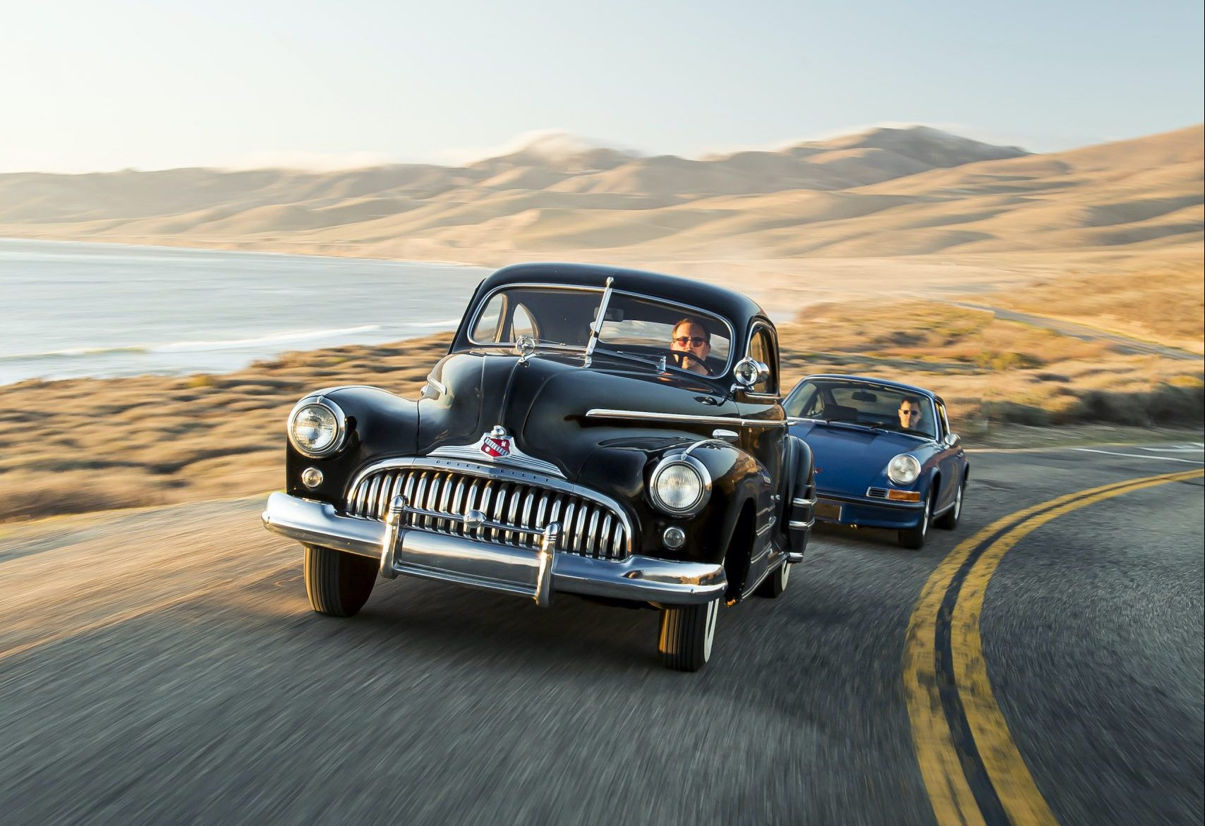 1946 Buick Special and 1970 Porsche 911 driving action vertical