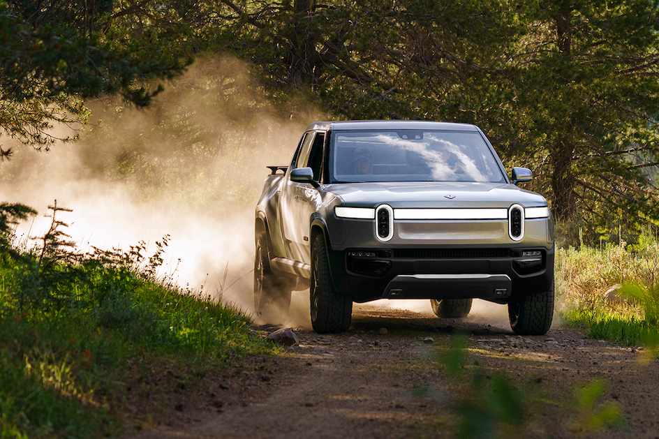 Rivian Pickup dirt road action front three-quarter