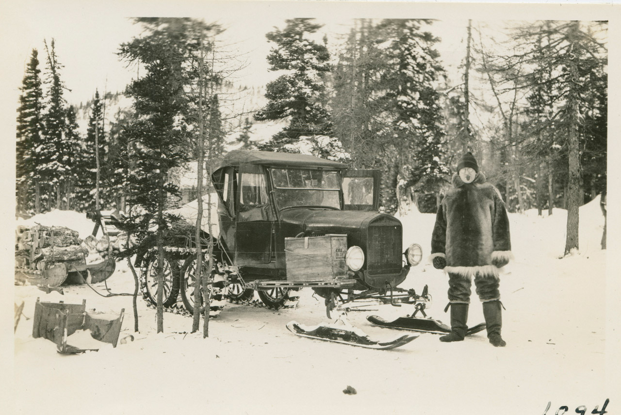 The Snowmobile ready for trip into Nain with cook Martin Vorse standing by with pipe. The oil box off the side of the engine utilized exhaust heat for cooking food.