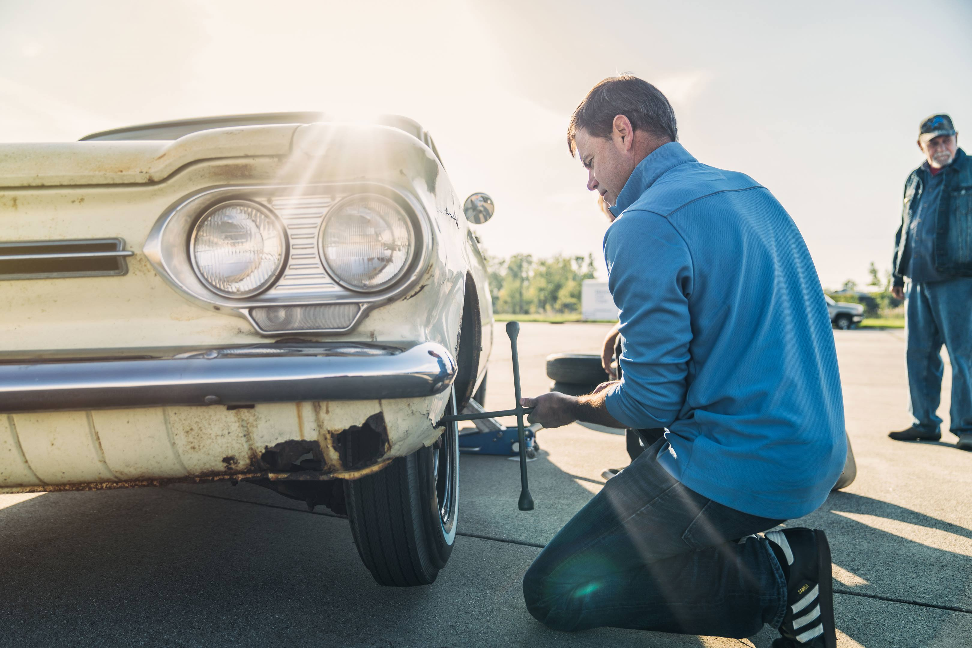 Larry Webster changing the tire on Ralph Nader's 1962 Corvair Monza
