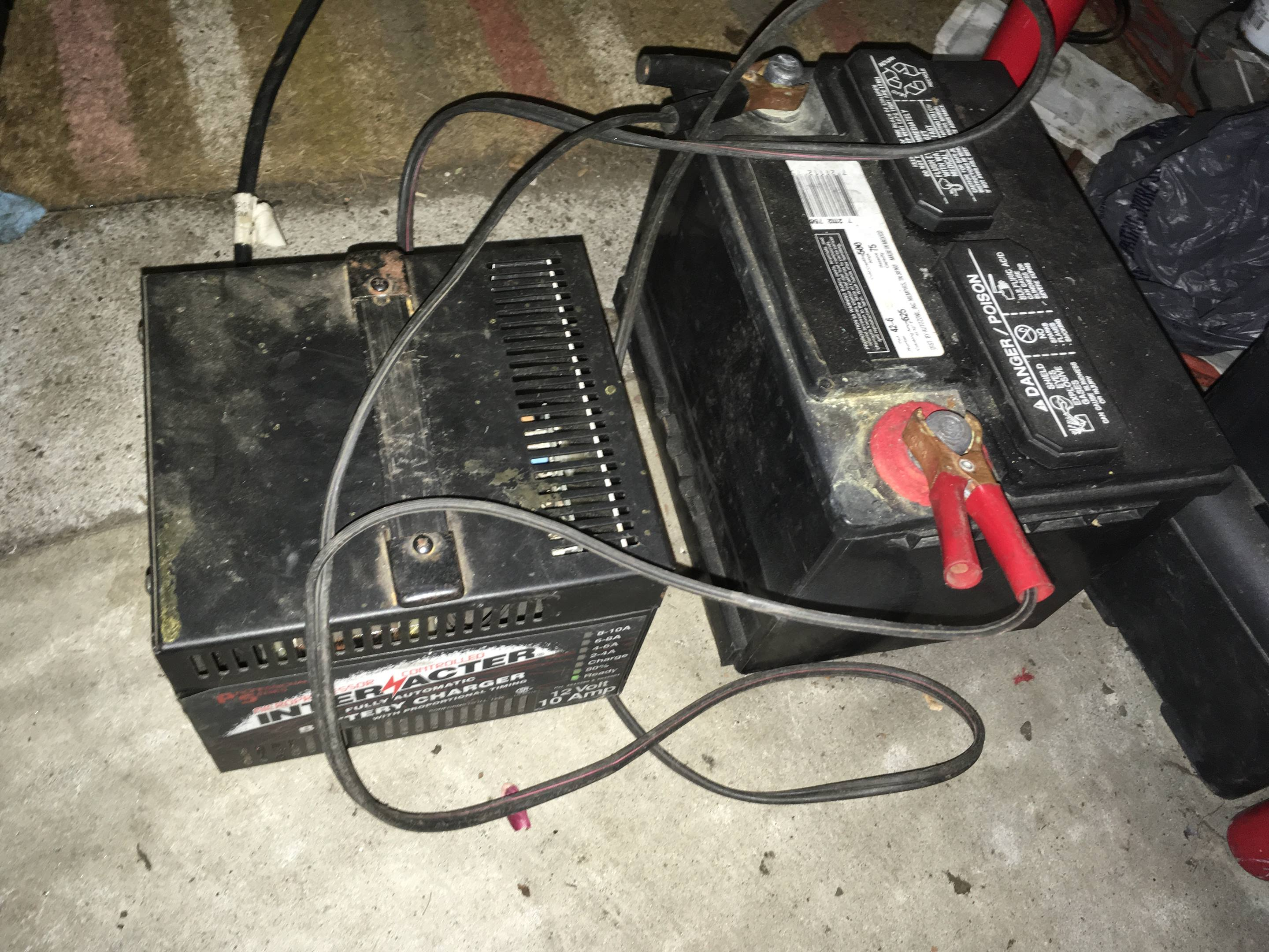 Feel free to leave or charge your battery on the garage floor. Concrete does not discharge the battery; that's a myth.