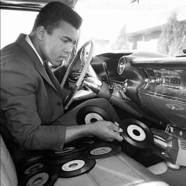 Muhammad Ali is shown jockeying singles into the Philips record player in his 1959 Cadillac Eldorado