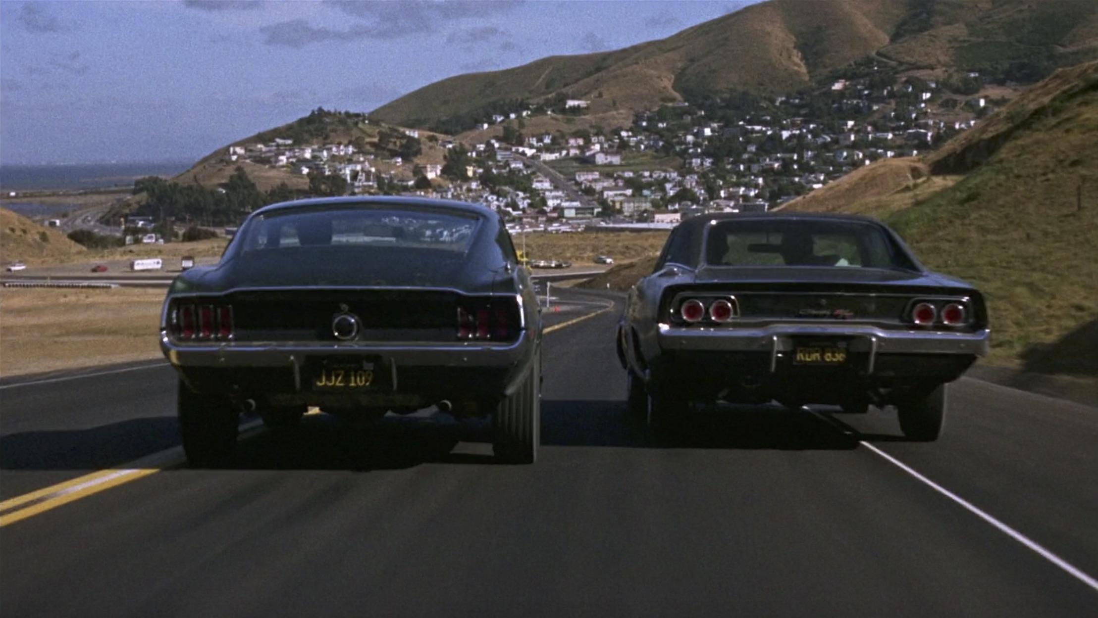 Bullitt Mustang racing away from a Dodge Charger