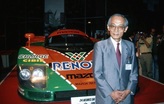 Kenichi Yamamoto in front of a Mazda race car