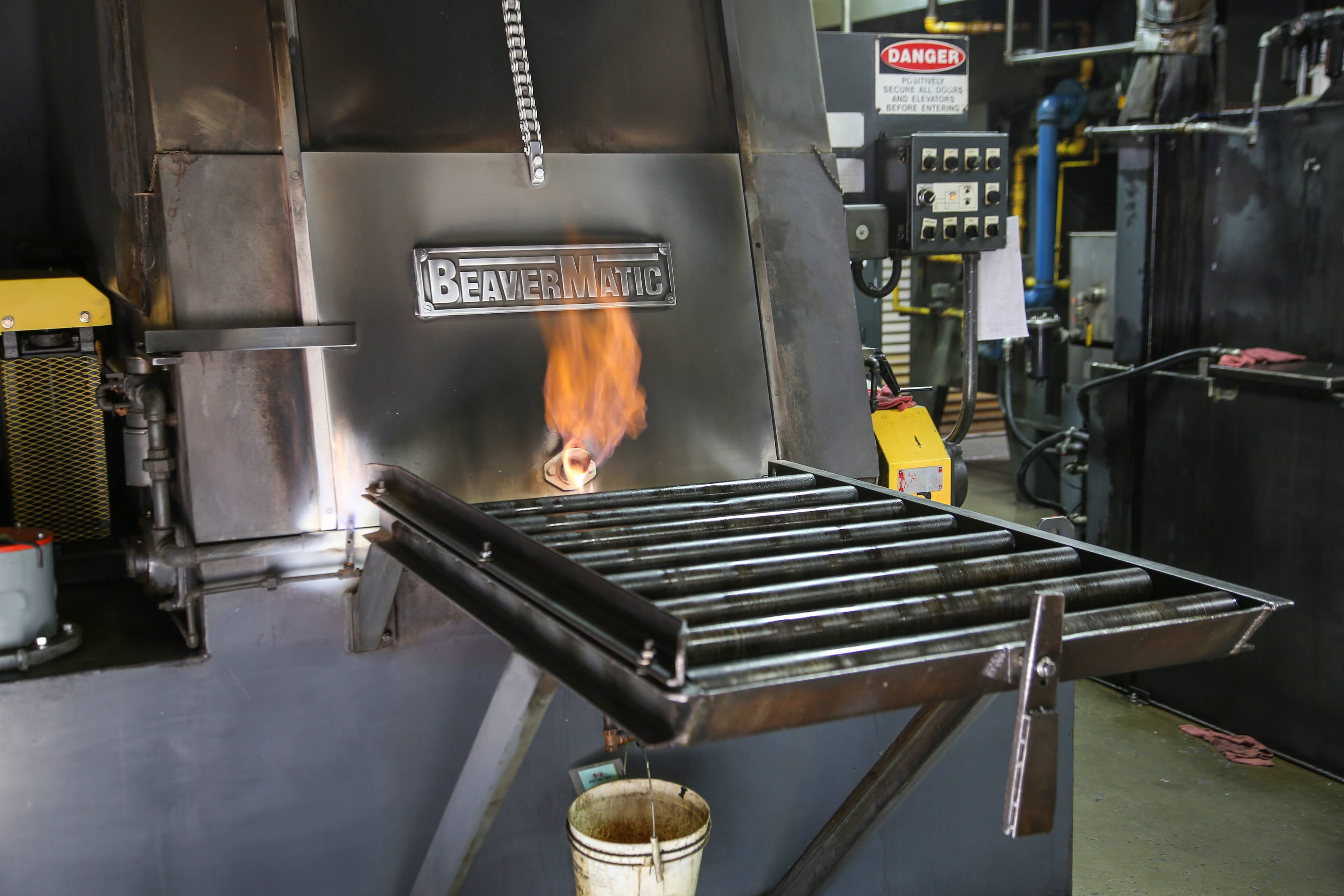 Parts are quenched in oil stored below the furnace. The flame at the door prevents outside air from contaminating the nitrogen atmosphere inside when the door is opened.