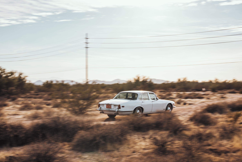 white 1974 Jaguar XJ6 driving away