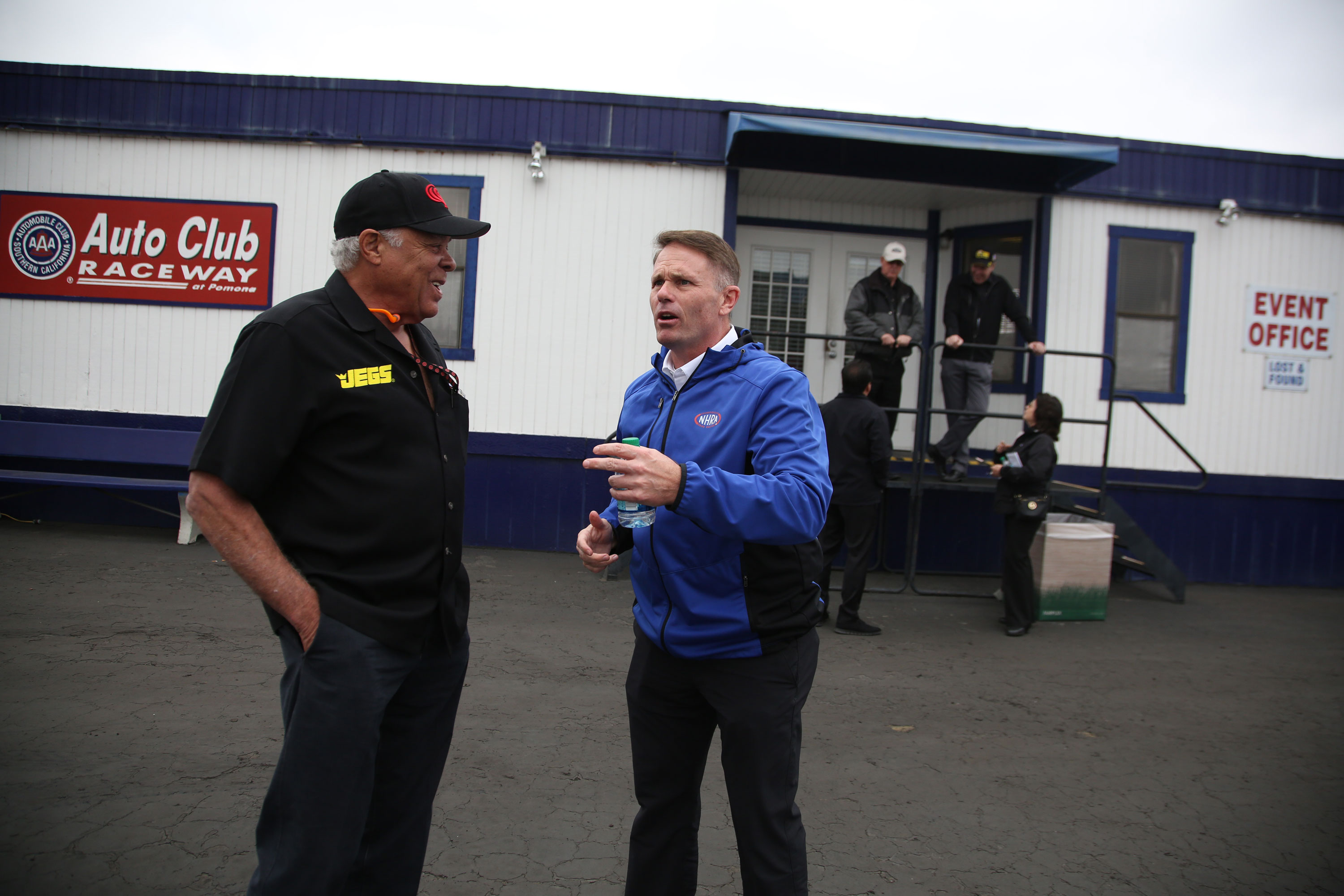 """Prudhomme jokes with NHRA president Glen Cromwell--who greeted Prudhomme by holding out his wallet and saying, """"Just take it,"""" a reference to Prudhomme's complaints about the payscale for race appearances. """"Hey man, I got car payments,"""" answered Snake."""