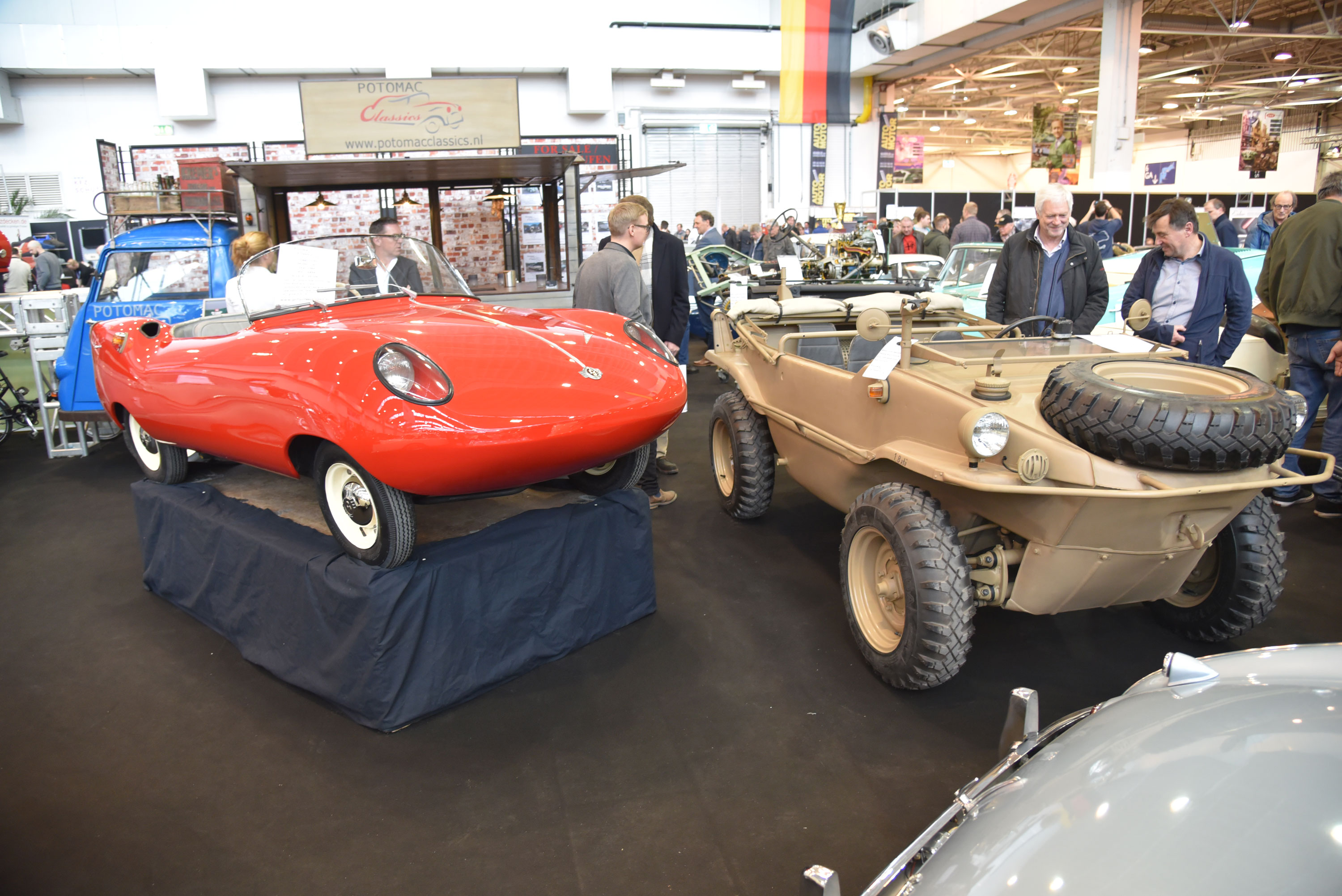 """In the weird-and-German department, a 1960 Goggomobile Dart based on a Geraman Goggomobile microcar chassis but actually built in Australia, and a World War II VW Type 166 Schwimmwagen (literally: Swimming Car) shared a booth. With its 392-cc two-cylinder two-stroke engine on the back axle, the 800-pound Dart was built for three years with around 700 made, while the """"Schwimmer"""" was basically an amphibious form of the VW Kubelwagen. Both are highly collectible today."""