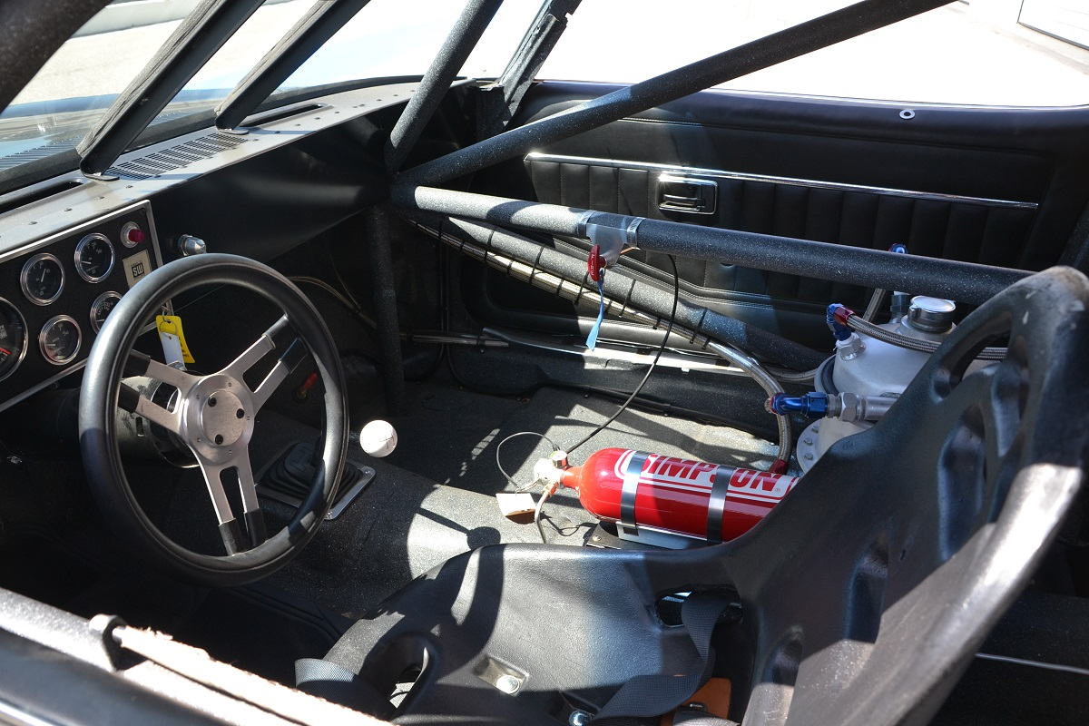 What started as a stock Camaro interior was stripped and gained roll cage, racing seat, and fire bottle. The oil tank for the dry sump system took the place of the passenger seat.