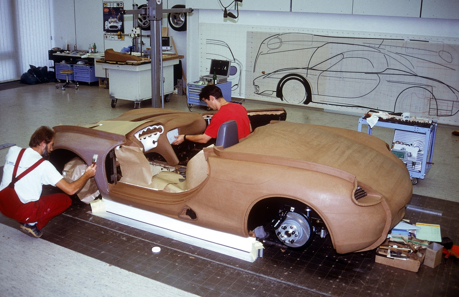 In a later photo of the clay model, the Boxster concept's five-gauge instrument panel, rocker panel air intake, and distinctive taillights are visible.