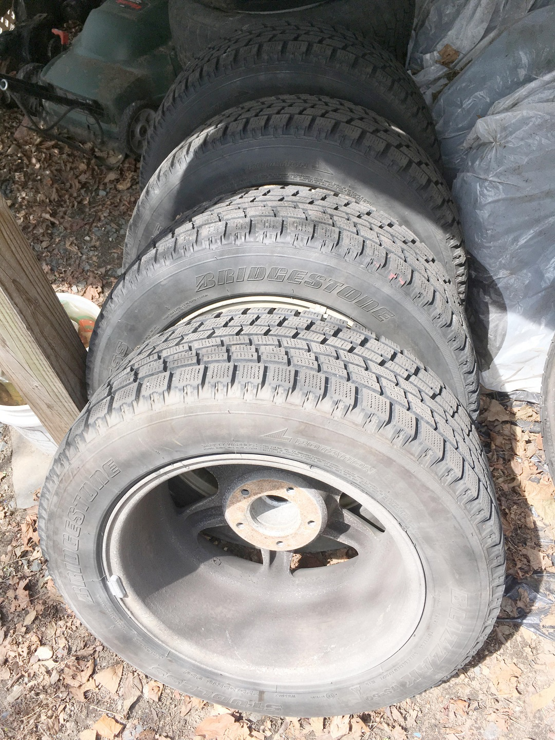 When storing tires outside, vertical is better, as there's much less chance of moisture getting trapped between them. Bagging them or tarping them is even better.