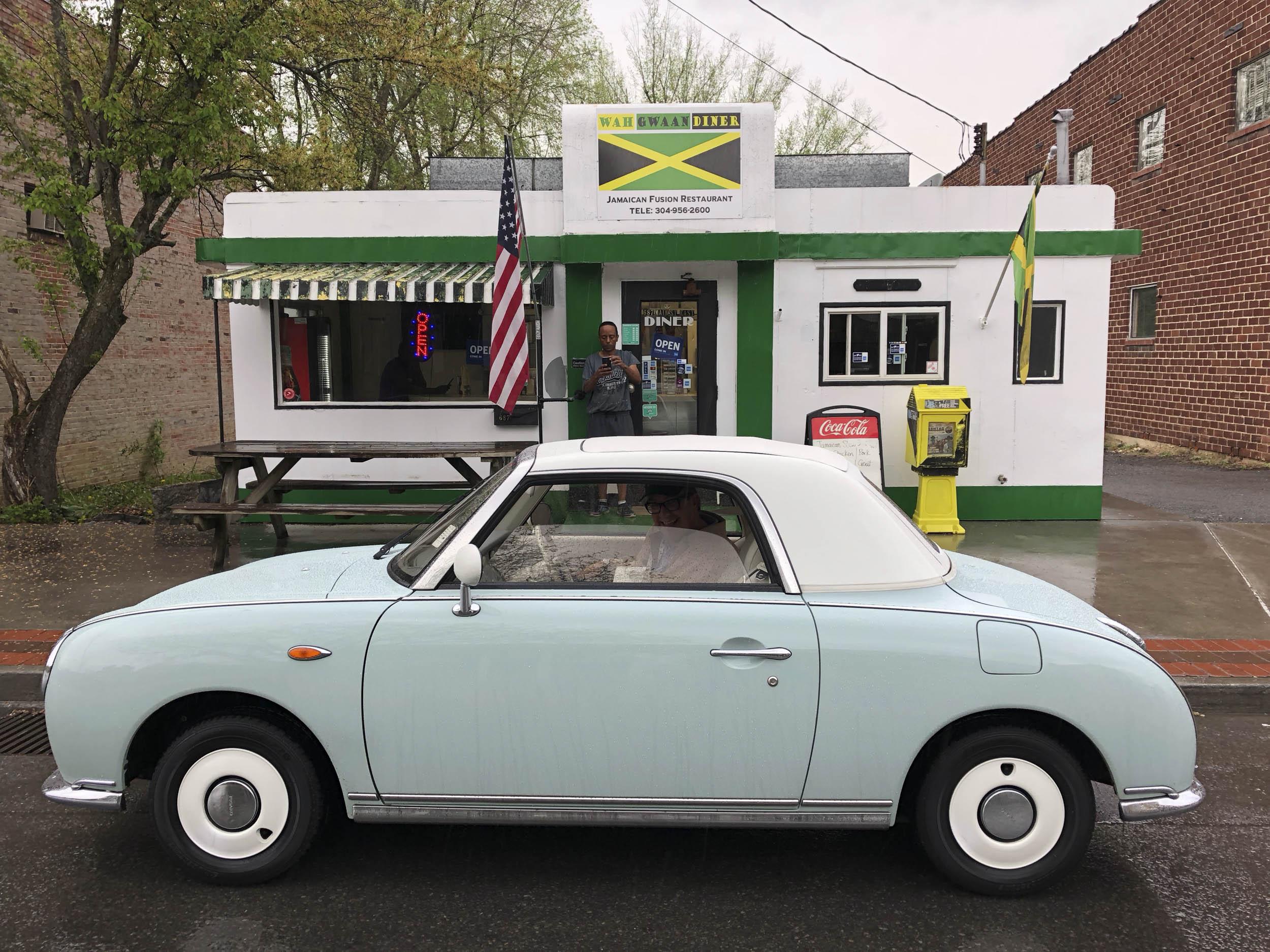 Larry Printz driving a 1991 Nissan Figaro around town