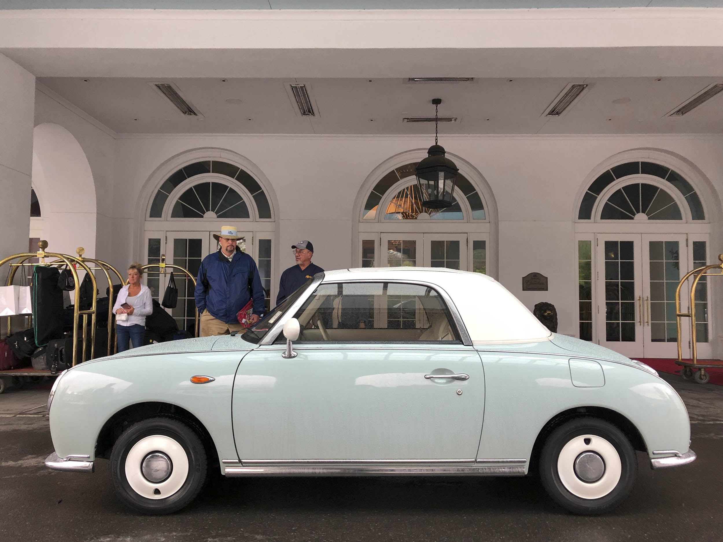 1991 Nissan Figaro outside of a hotel loby