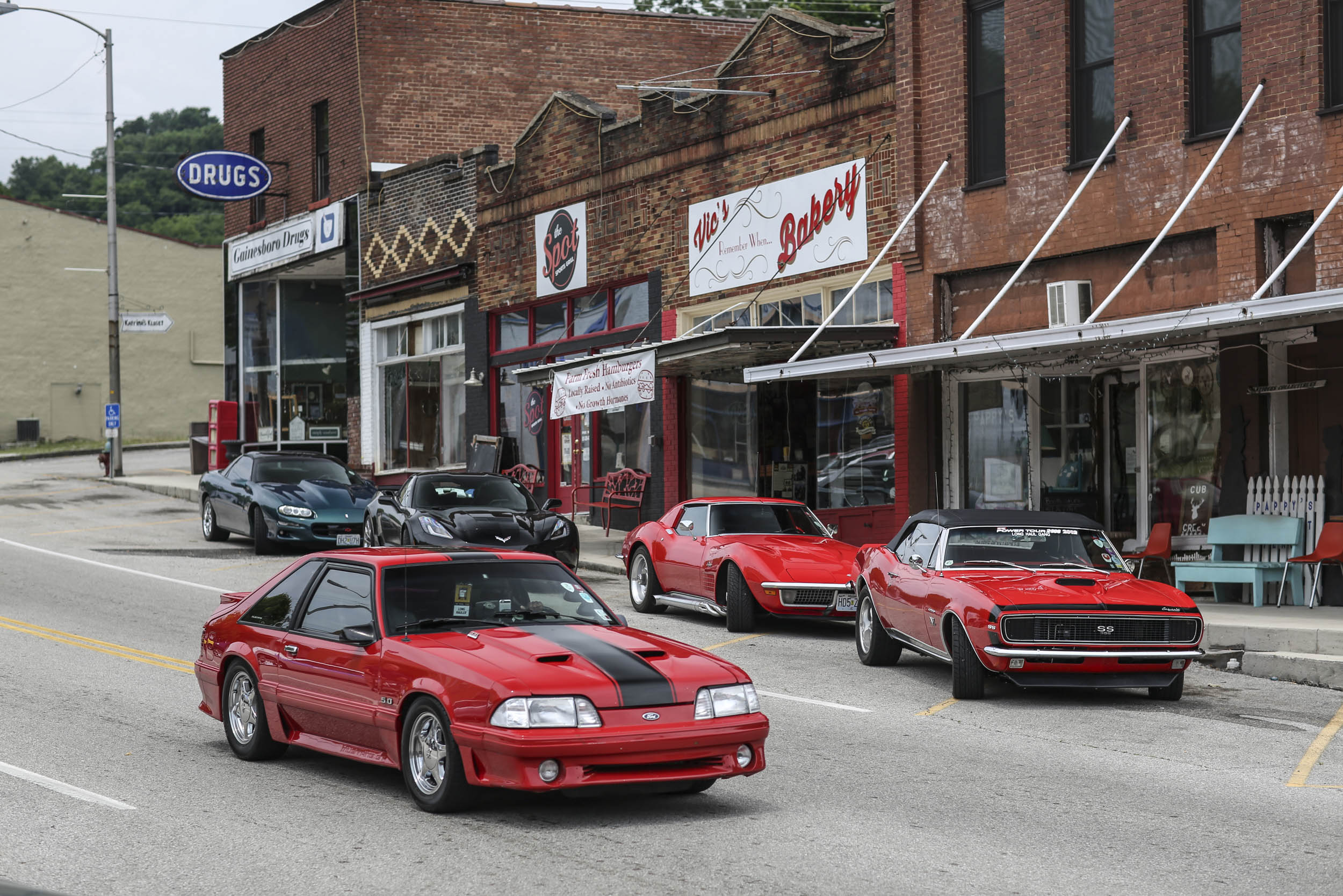Performance cars line the block and fill the street. These kinds of scenes are common all along the Power Tour route.