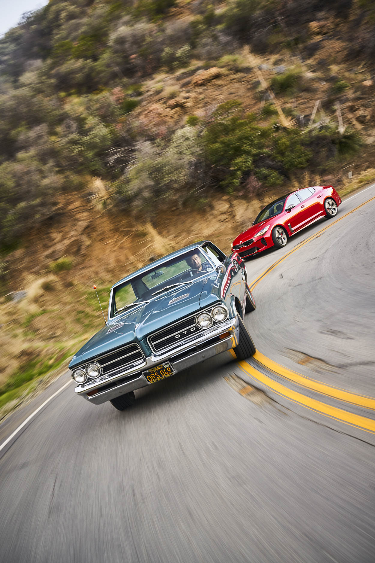 What looks like a lovingly restored '64 GTO in front of ordinary traffic is, in fact, a pairing of two cars on similar missions separated by five decades, here running Mulholland Highway near Los Angeles, scene of many a street race back in the day.