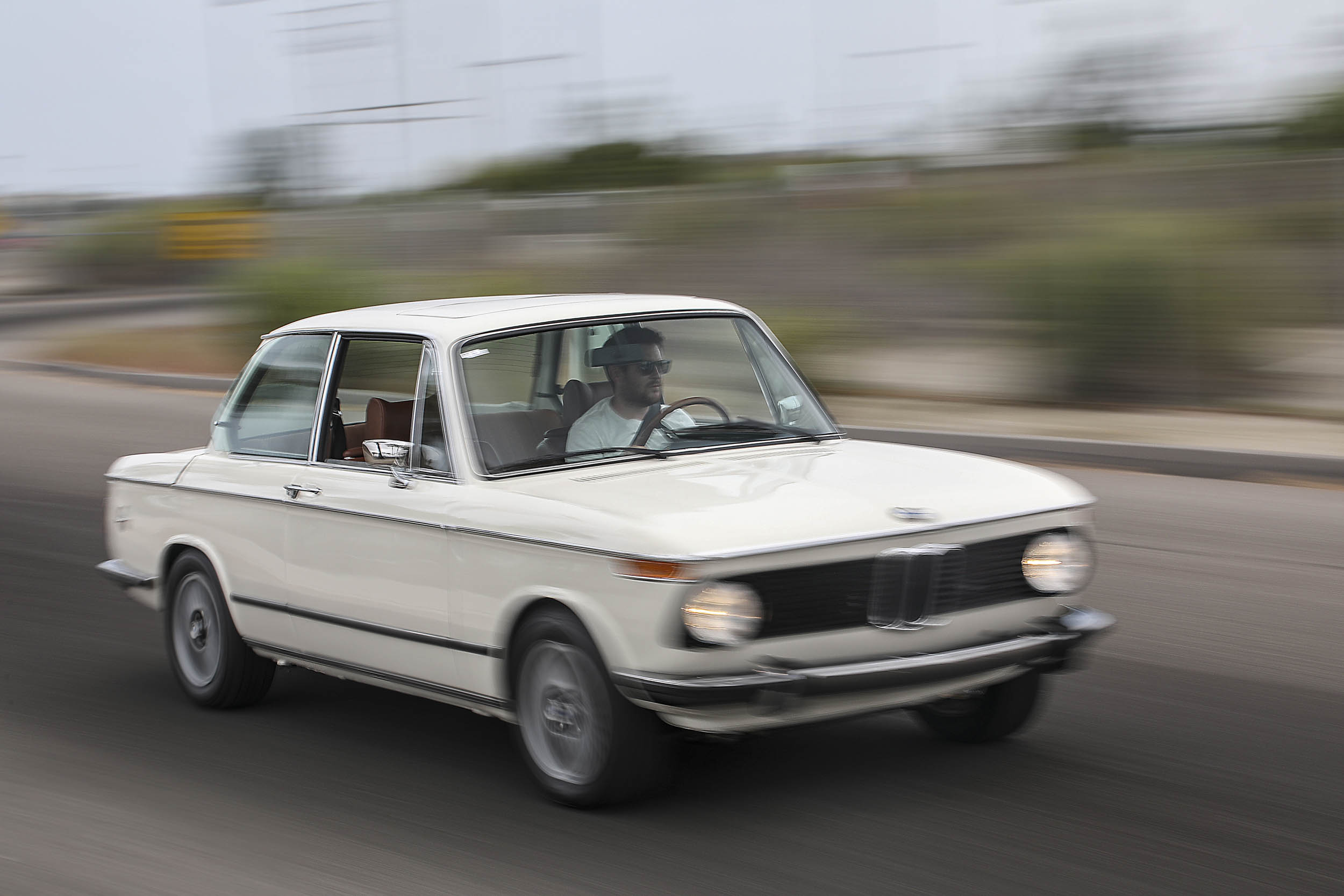 1975 BMW 2002 driving front 3/4