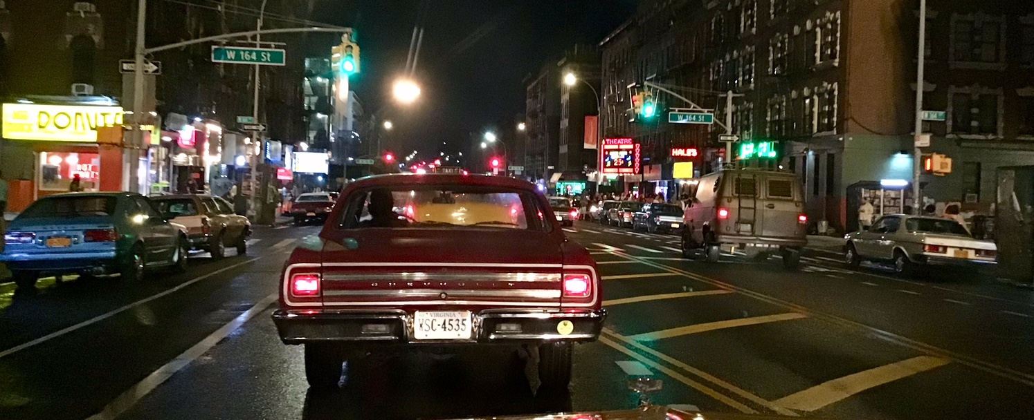 Period cars drive down Amsterdam Avenue in New York City dressed up like Times Square in New York City.