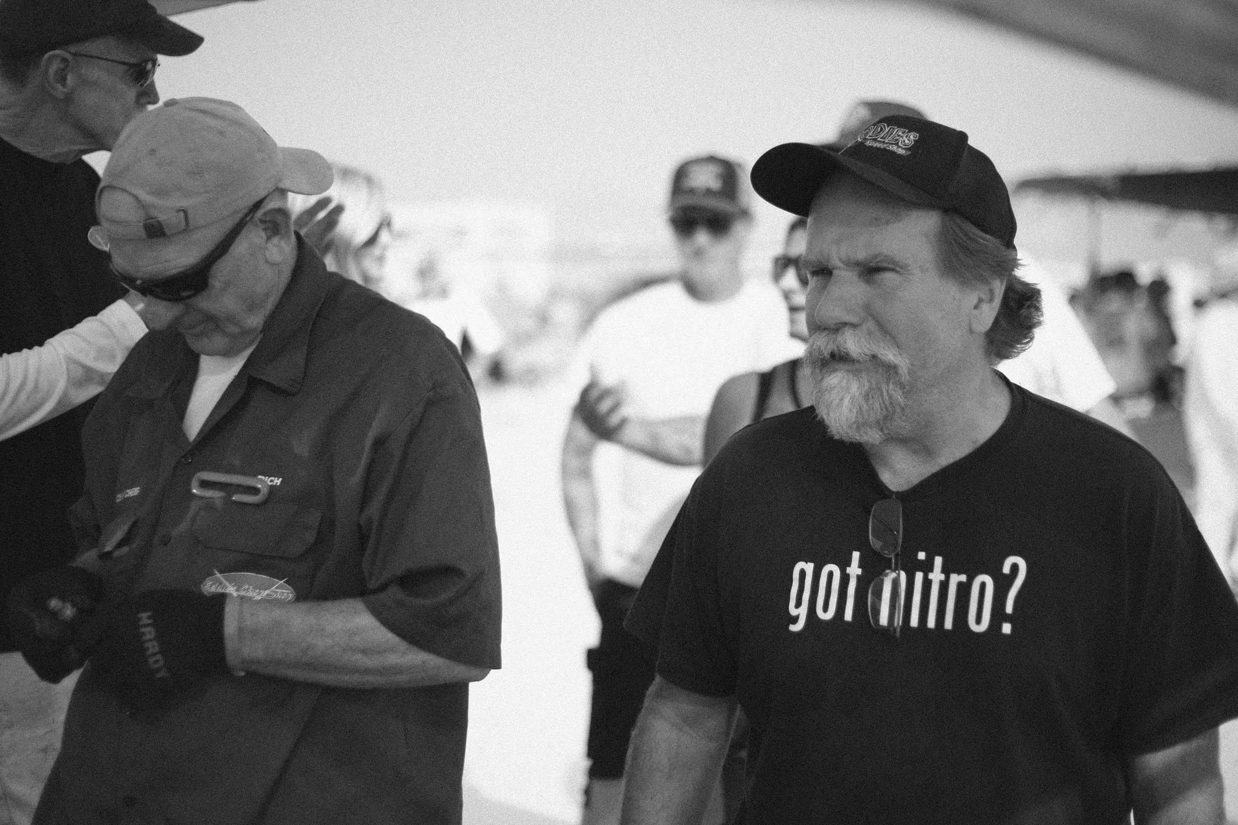 Bob Dalton checks in on fellow racer Eddie Umland as the tech inspectors validate his engine displacement