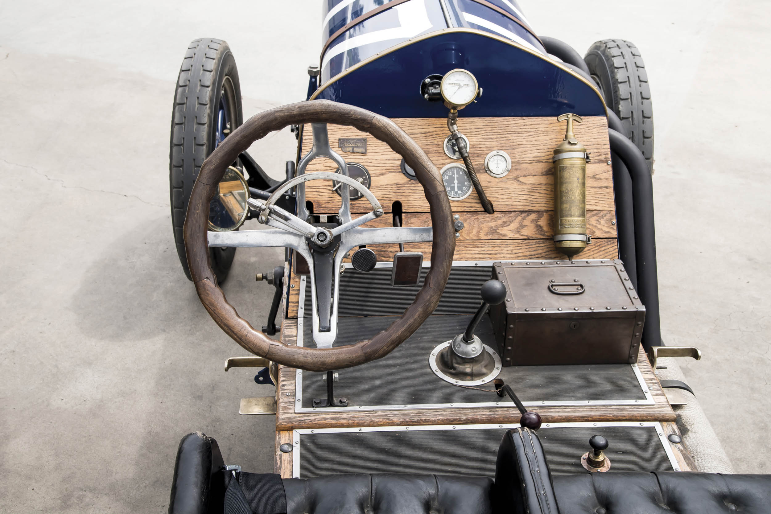The old-time cockpit of a 1916 National includes a box for tools and a fire bottle. One of the mechanician's jobs is to periodically pump water into the thermosiphon radiator.