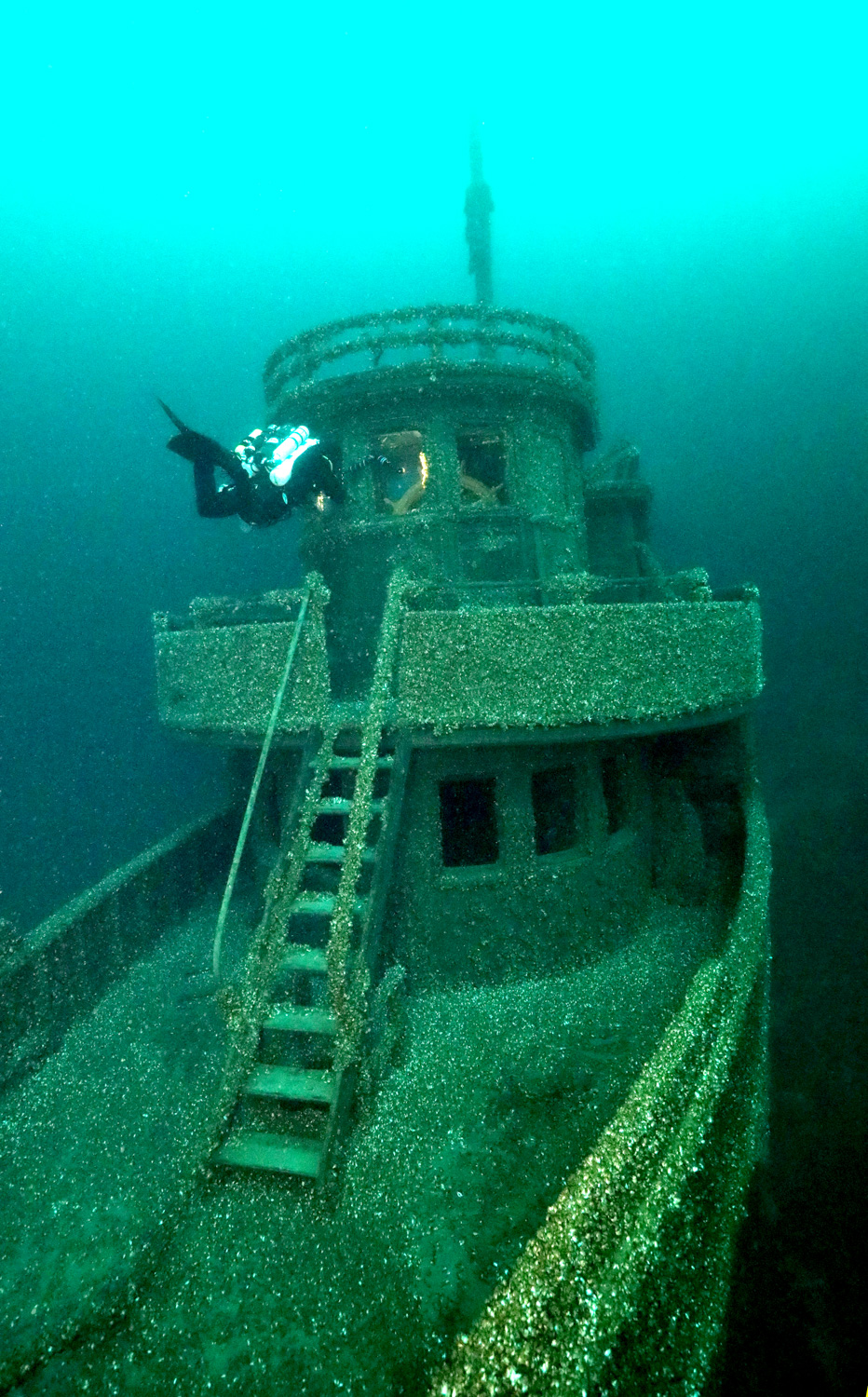 A technical diver approaches the intact pilot house and its unusual mid-ship stairway (which was a 1928 modification) on the MANASOO's bow.