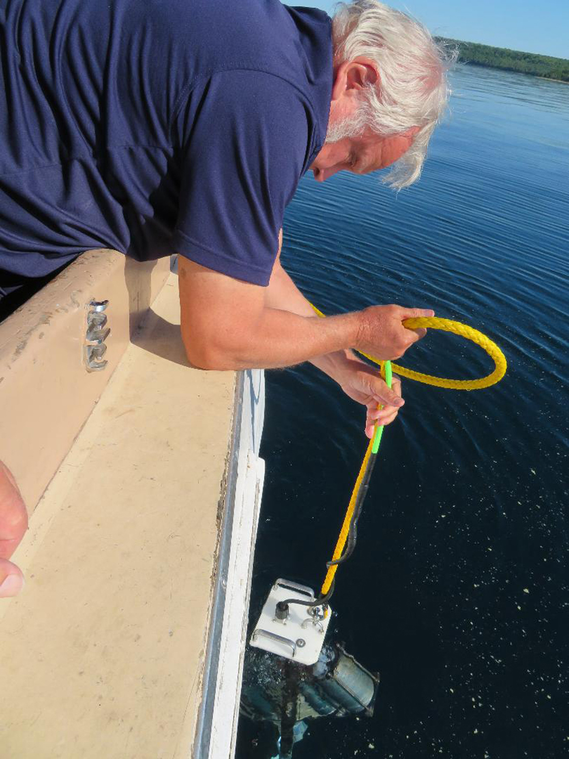 Cris Kohl carefully lowers Jerry Eliason's underwater video camera and lights so the team on the boat can view the wreck of the MANASOO without even getting wet!