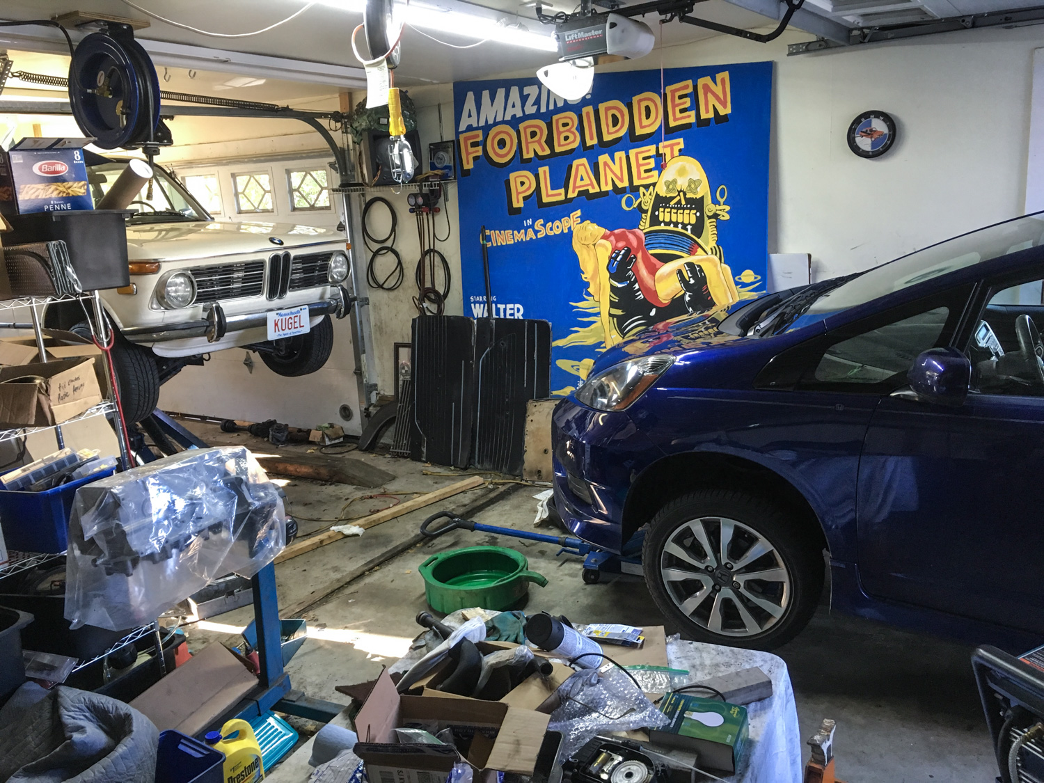 Because the mid-rise-lift is almost always occupied with a project car, maintenance on daily drivers is often performed with just the nose of the car in the garage.