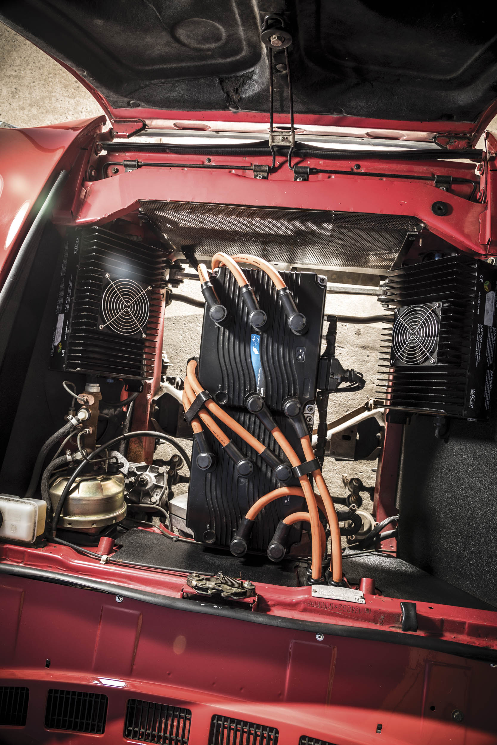 Under the hood of this Fiat 2000 are a pair of inverters with high-voltage cables standing in for spark-plug wires. The fans on either side cover the chargers.