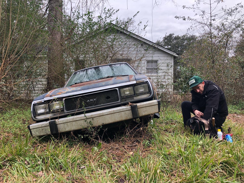 jacked up amc amx derelict car