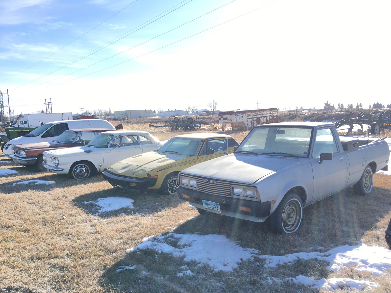 snow covered derelict cars in field