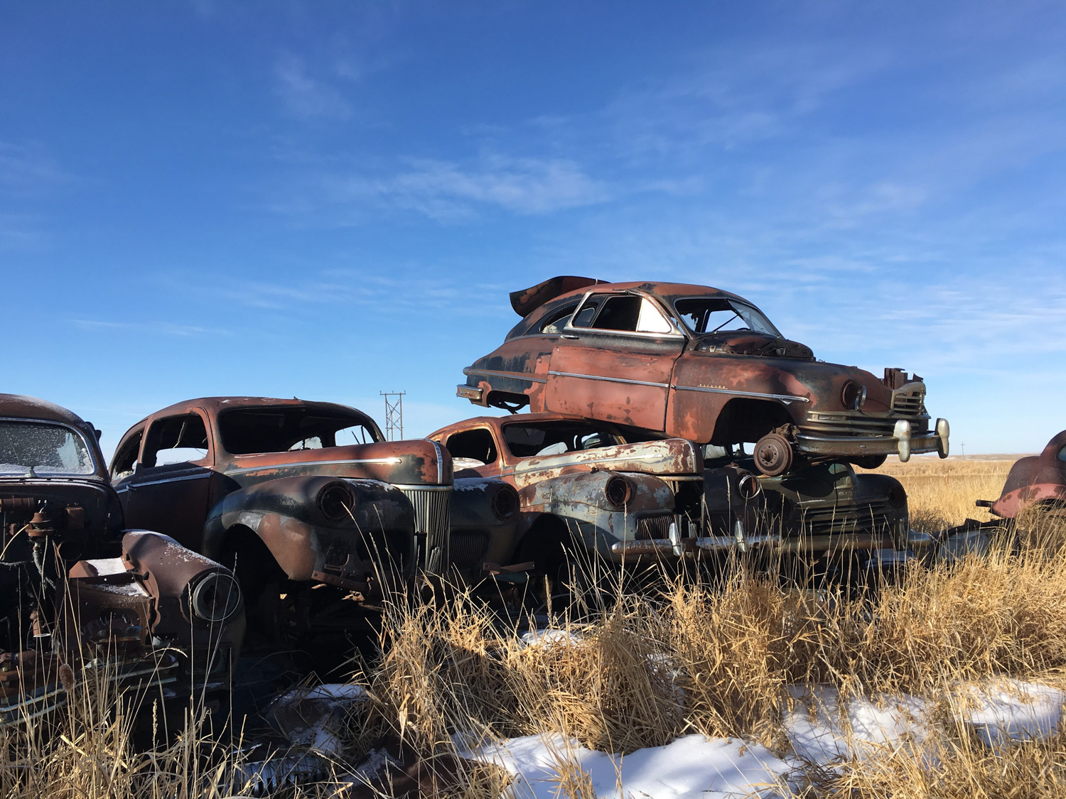 derelict 1940s american cars stacked