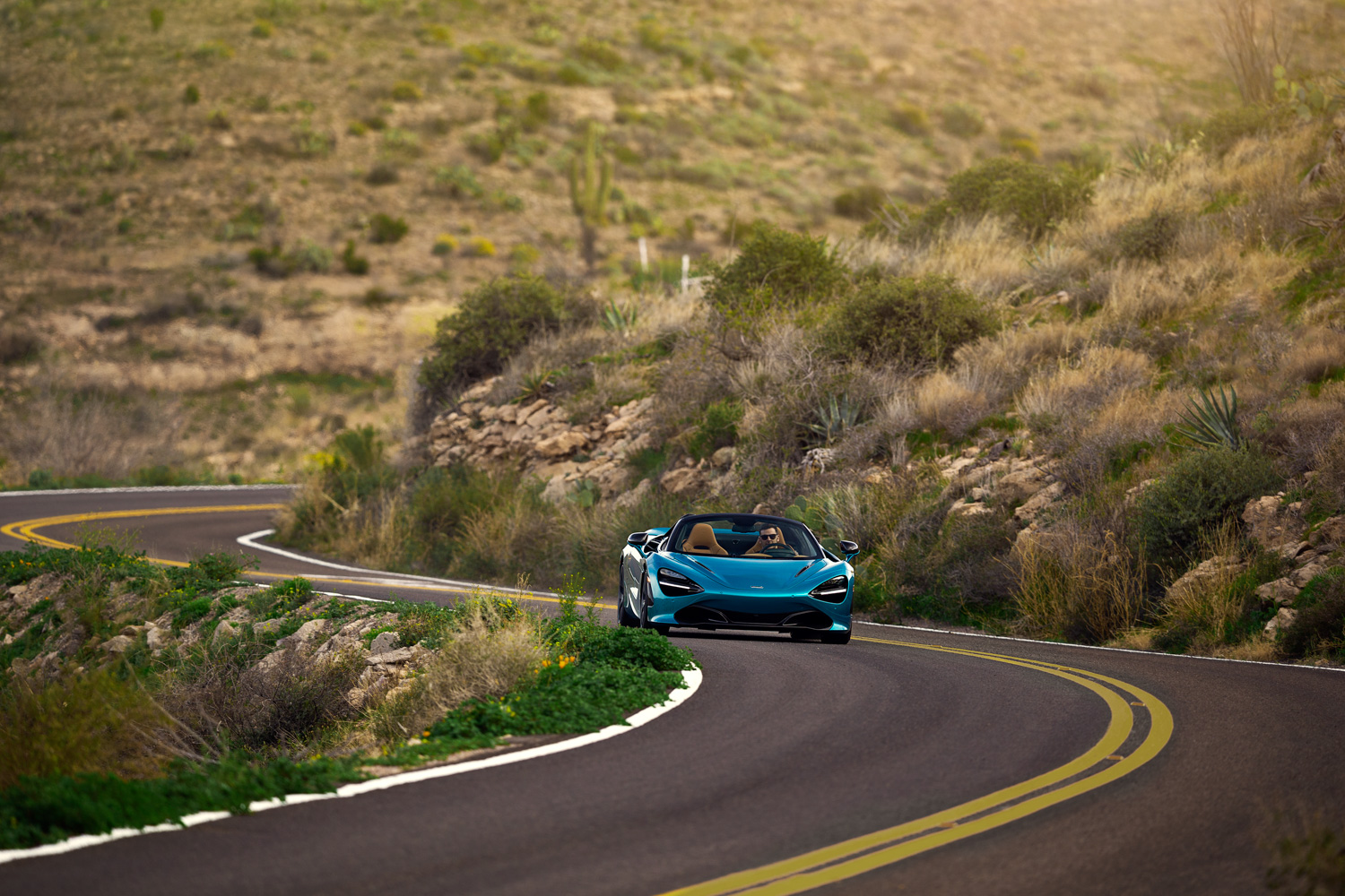 McLaren 720S Spider on road driving front blue