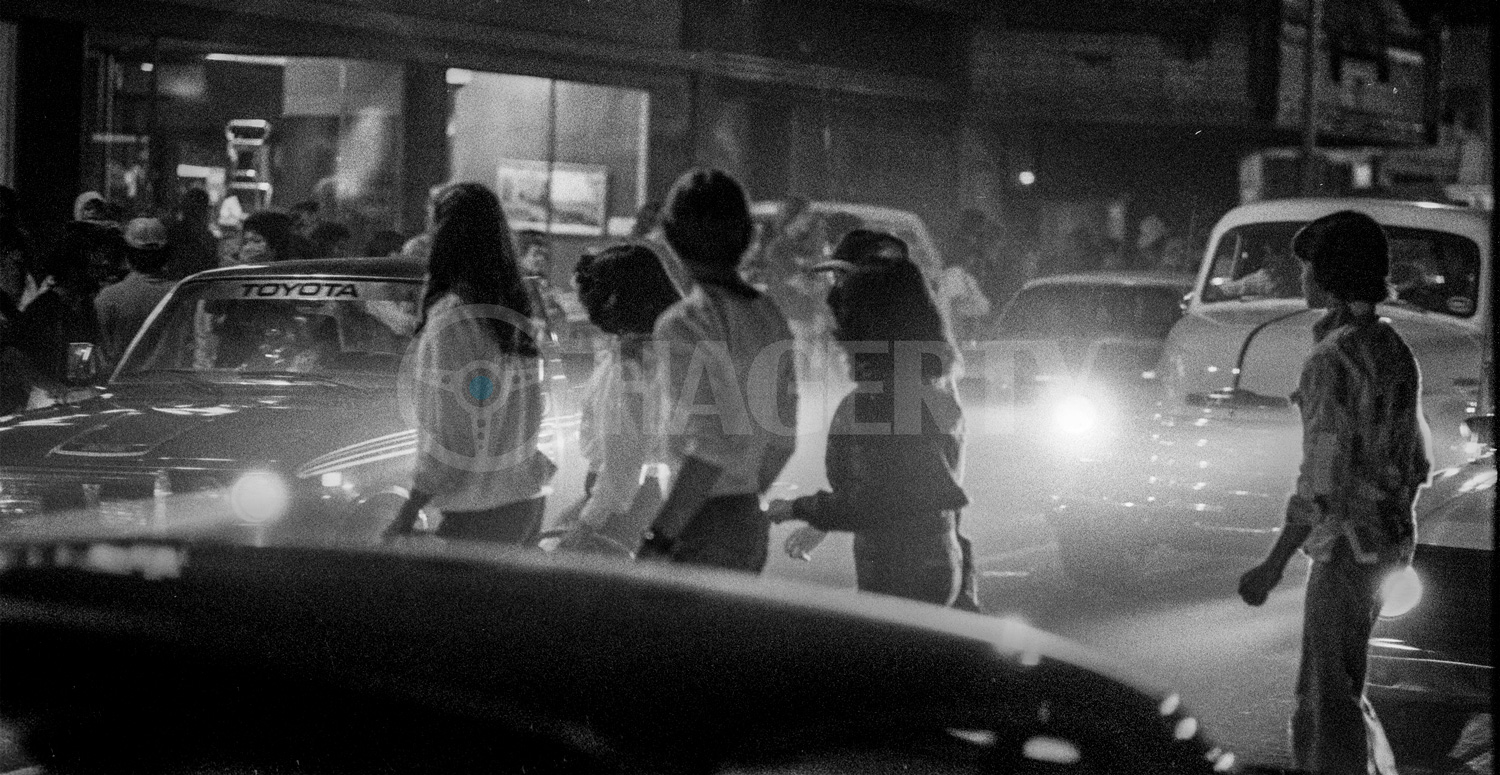 """A pack of local teens struts in front of cruising classic cars in 1979. This annual event paying homage to the 1973 film American Graffiti is traditionally held the weekend after graduation at Modesto's Central Valley High School. """"Those kids are grandpas and grandmas now,"""" says Golub, who still lives in the area."""
