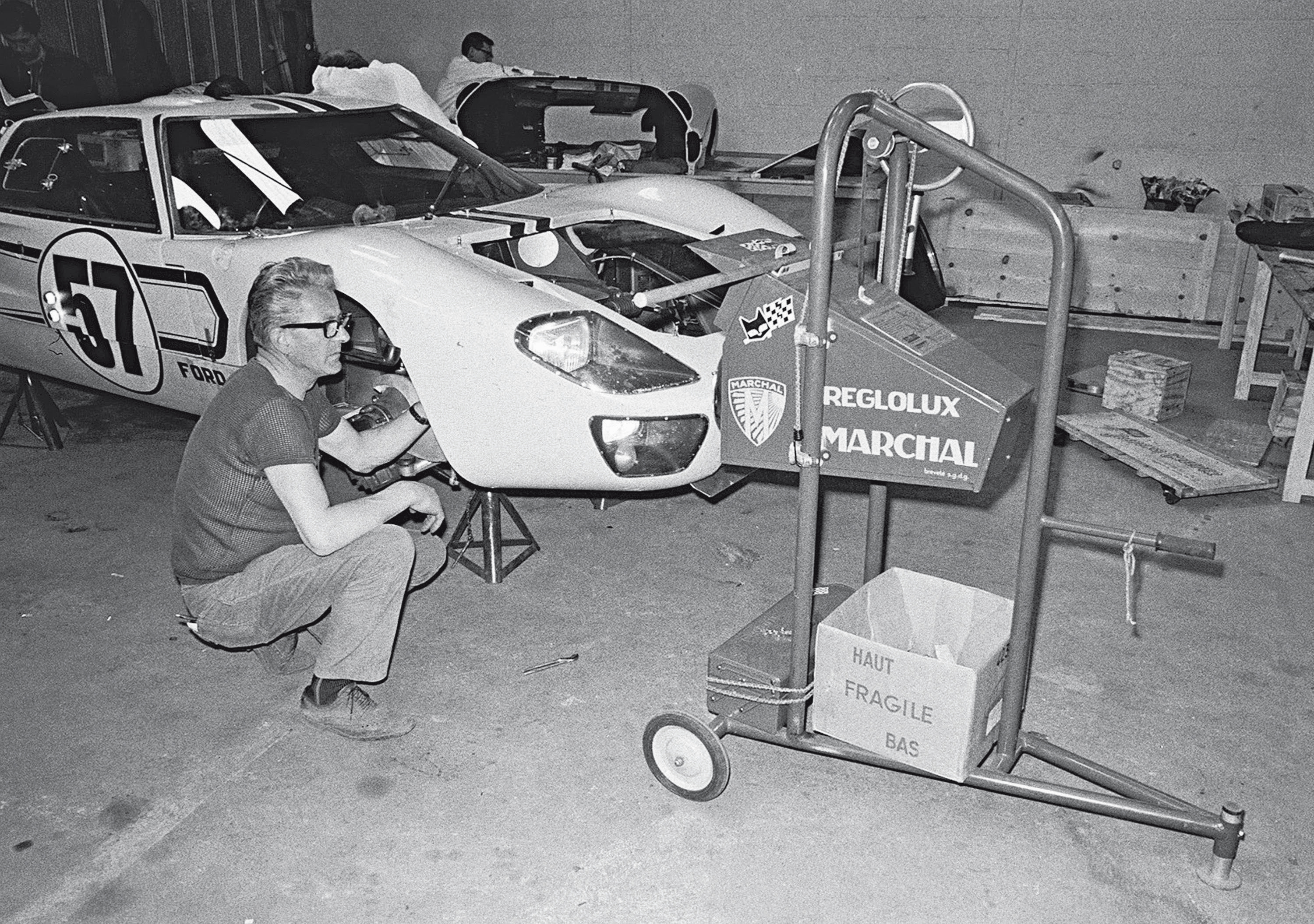 A technician checks the headlight alignment on the Ronnie Bucknum/Paul Hawkins Mark IIB in the Ford garage. The standard practice was to aim the headlights outward toward the trees that lined the circuit.