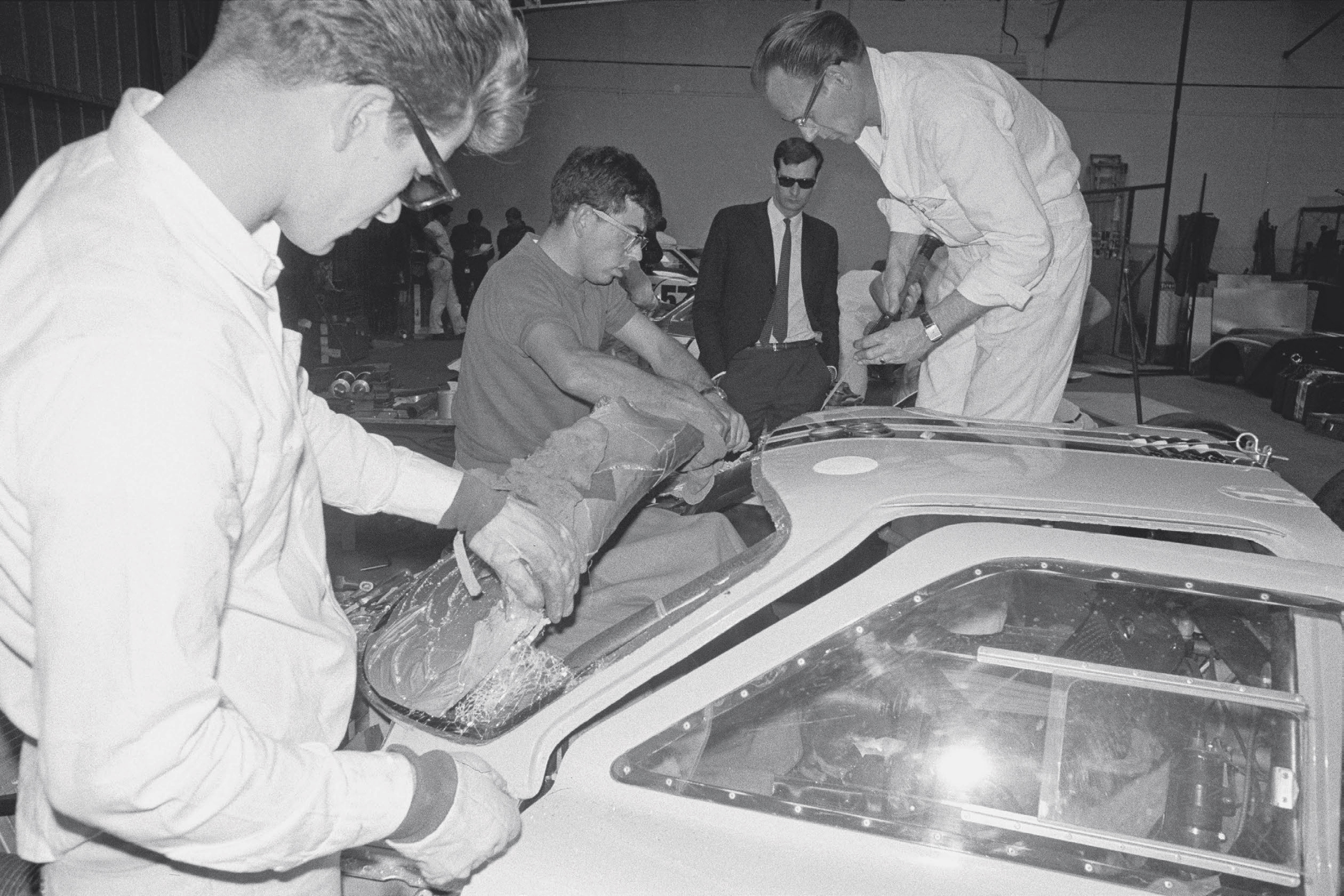 The windshields in the Fords started cracking as soon as practice began. An extra-hard temper had made the glass too brittle, and Dow Corning produced replacements on an emergency basis. Here, Gordon Chance, Charlie Agapiou, and Max Kelly (left to right) replace the windshield on the Bruce McLaren/Mark Donohue Mark IV.