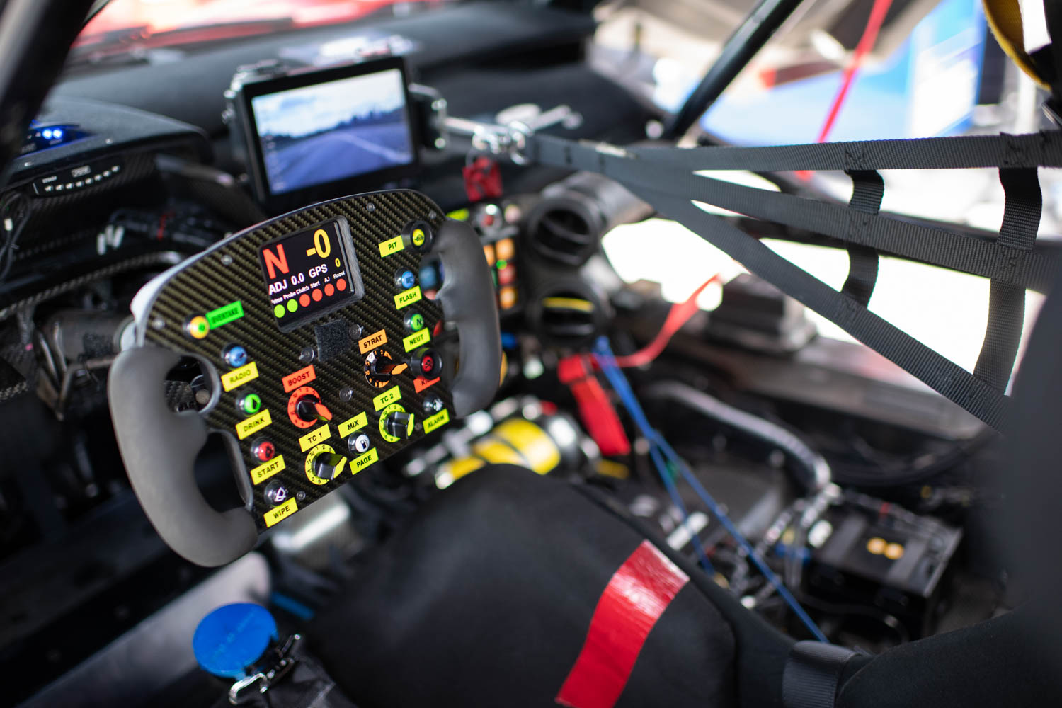 The GTLM's steering yoke— wheels are passé—is the car's command center. The screen in the background displays the rear view.