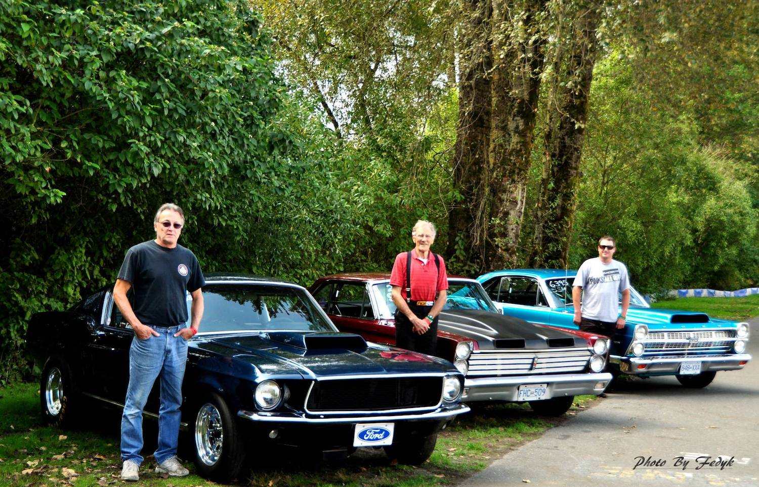 generational racers standing beside cars