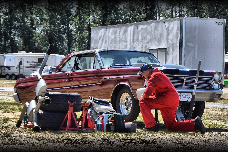 man working on comet drag car