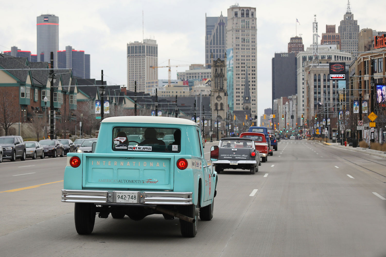 classic cars driving to downtown detroit