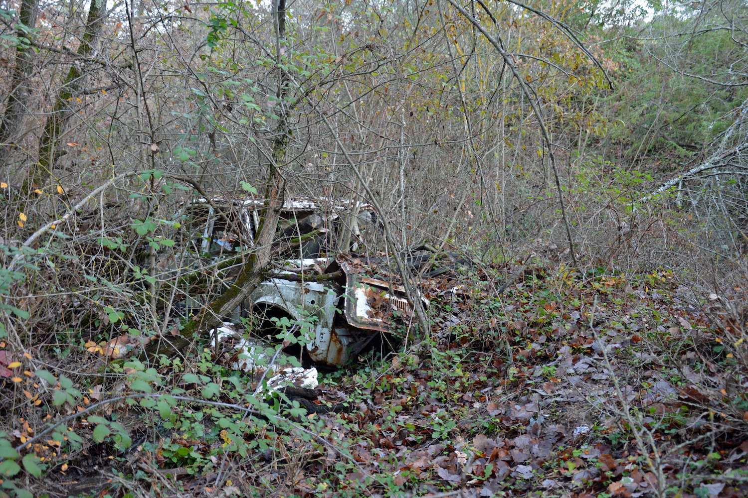 abandoned buried old car front three-quarter
