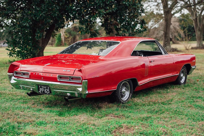 1966 red pontiac 2 plus 2 rear three-quarter
