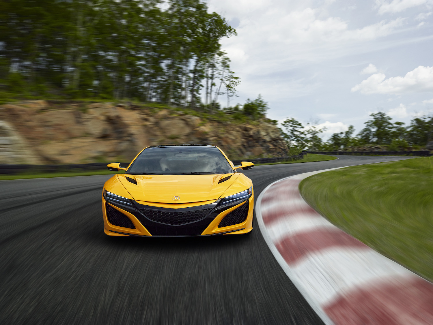 yellow 2020 acura nsx on track in motion front three-quarter