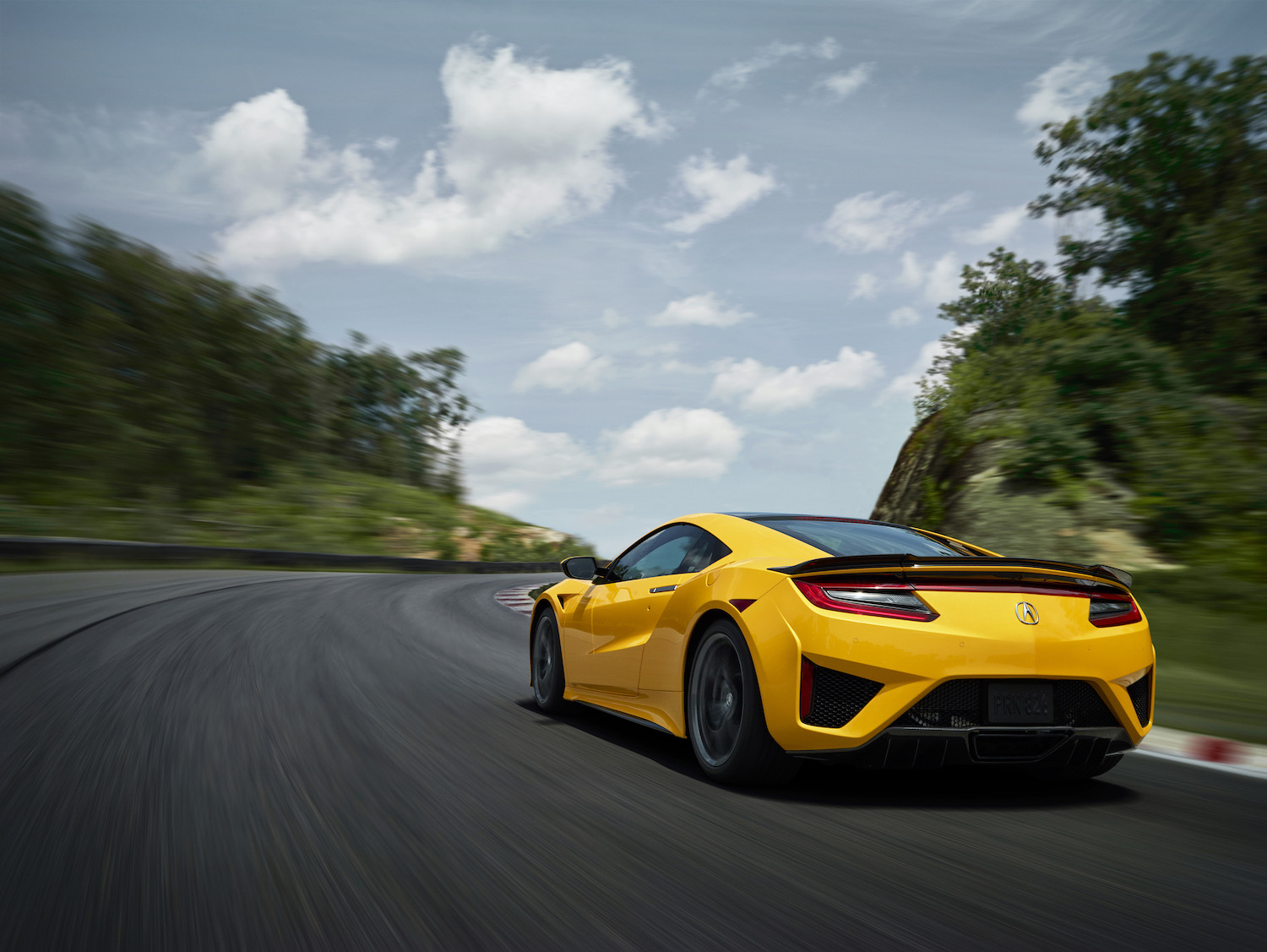 yellow 2020 acura nsx on track in motion rear three-quarter