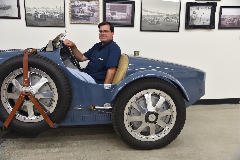 man sits in vintage roadster